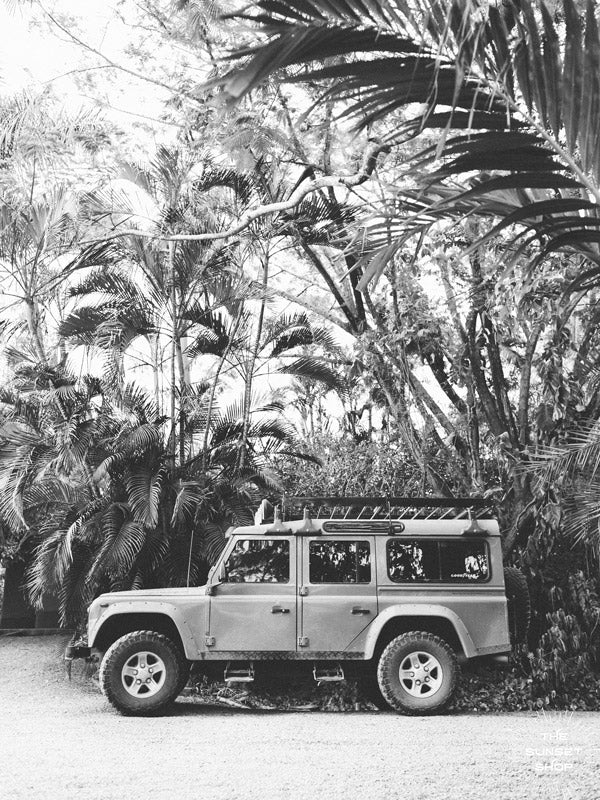 "Because life is all about the magic in the detours and the beauty of taking time to explore bumpy, back road dirt roads in tropical paradise with Land Rover Defender just like this. ""Tropical Sleigh"" black and white Land Rover photo print photographed by Kristen M. Brown, Samba to the Sea for The Sunset Shop."