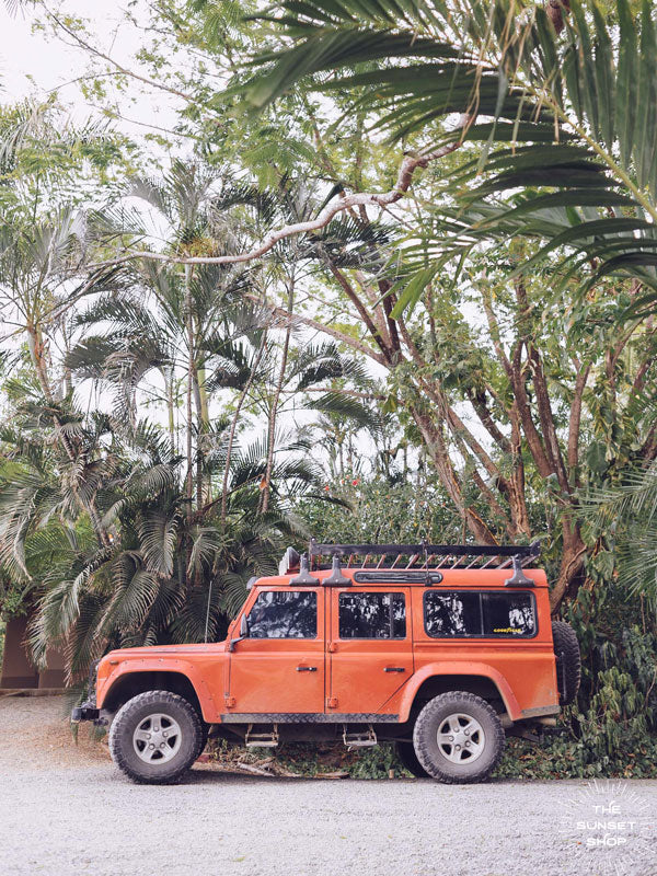 "Because life is all about the magic in the detours and the beauty of taking time to explore bumpy, back road dirt roads in tropical paradise with a vibrant red Land Rover Defender just like this. ""Tropical Sleigh"" photographed by Kristen M. Brown, Samba to the Sea for The Sunset Shop."