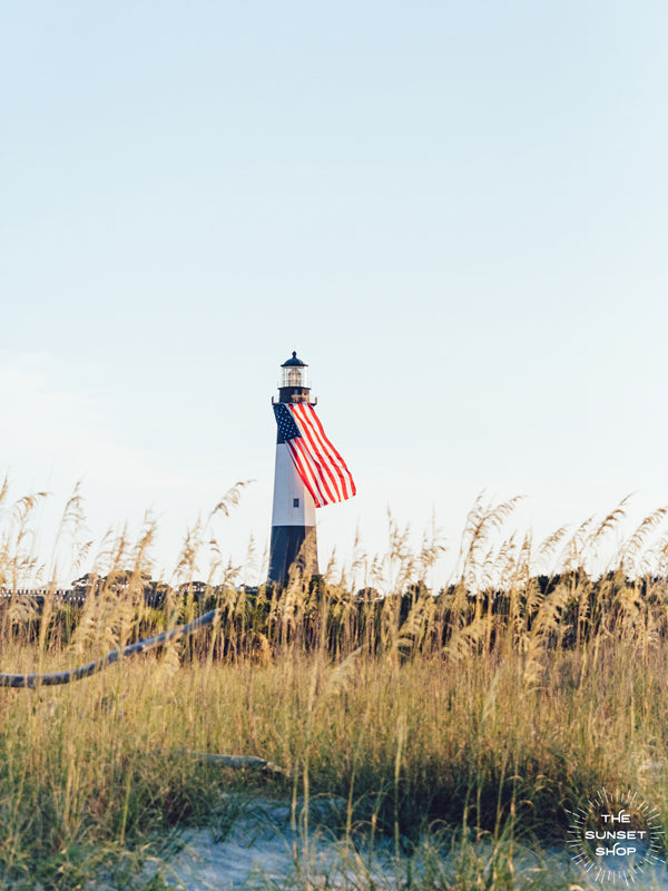 "There she was, dancing in the sea breeze with the sea grass and shimmering in the late afternoon sun! Majestic American flag hanging from the Tybee Island Lighthouse in Tybee Island, GA. ""Tybeautiful"" photographed by Kristen M. Brown, Samba to the Sea for The Sunset Shop."