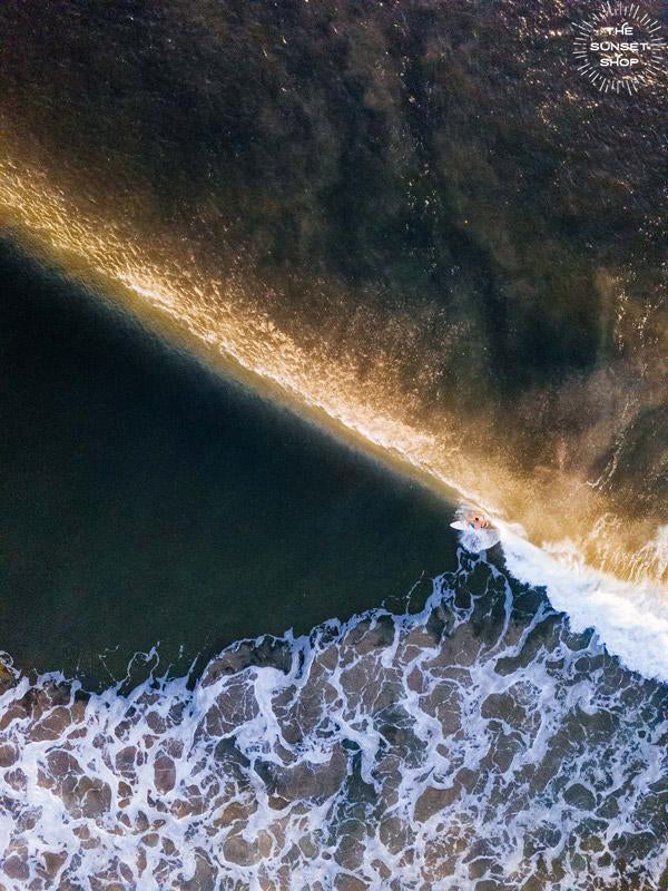 Aerial surfer print by Samba to the Sea at The Sunset Shop. Image is an aerial photo of surfer dropping in on a wave in Tamarindo, Costa Rica.