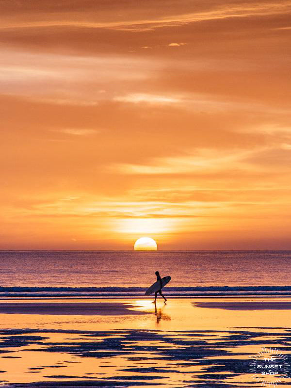Surfer walking on the beach during an orange sunset in Costa Rica. Walking On Sunshine sunset photo by Samba to the Sea at The Sunset Shop.