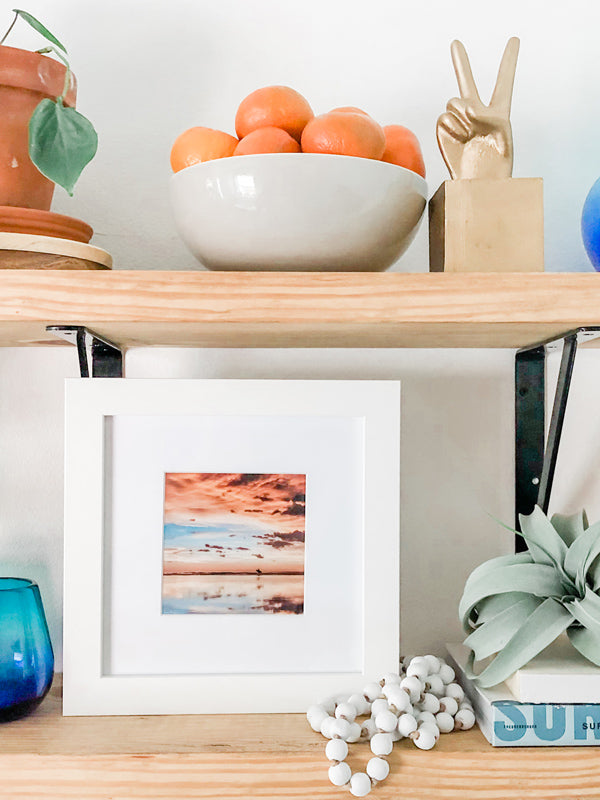 "Surfer sunset shelfie print on open shelving. Surfer walking on the beach during a beautiful sunset in Costa Rica. Sunset surfer print by Samba to the Sea at The Sunset Shop. ""Where the Sky Meets the Sea"" surfer sunset print by Kristen M. Brown, Samba to the Sea. Styled by Southern Mesa Trading."