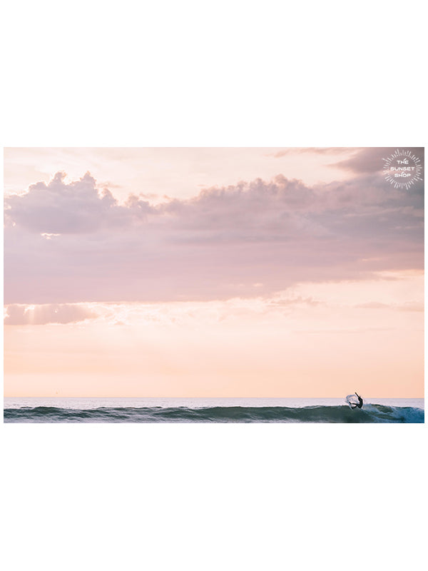 Surfer on a turquoise wave during a rosé sunset in Costa Rica. Yes Wave Rosé sunset surfer wave print by Samba to the Sea at The Sunset Shop. Image of a surfer doing a gorgeous snap on a turquoise wave during a beautiful sunset in Costa Rica.