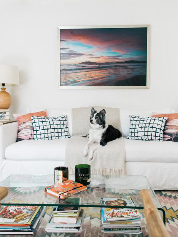 Beautiful beach sunset print in a boho chic living room with a Lulu and Georgia rug. You Had Me At Sunset fine art print by The Sunset Shop, Samba to the Sea.