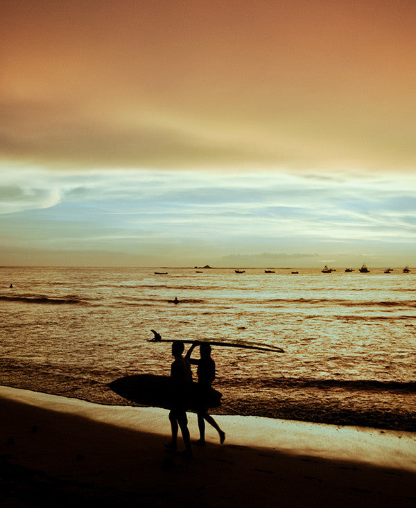 You, Me, and the Sea sunset print by Samba to the Sea at The Sunset Shop. Image of a surfer couple walking on the beach during a golden sunset in Tamarindo, Costa Rica.
