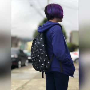 Tiny human with purple hair wearing skull and crossbones backpack facing away from the camera