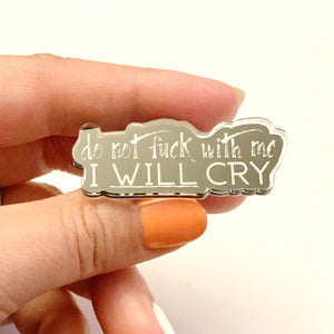Close up of fingers holding an I will cry pin