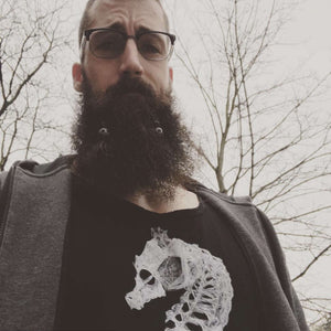 Bearded man wearing seahorse skeleton tank top with blazer
