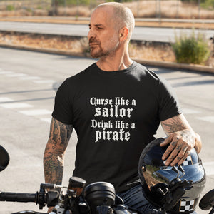 Man with shaved head sits on motorcycle with hemet under his hand. He has tattoos and wears a black shirt with the words curse like a sailor drink like a pirate in white letters.