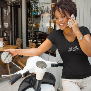 "Woman on mobile phone stands next to a scooter in a black v-neck shirt that reads ""do good recklessly"""