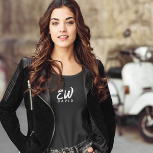 "woman with long dark hair wearing an ""Ew David"" short sleeve t-shirt with black jeans and a black jacket unzipped"