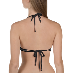 Woman facing away from camera wearing black side of reversible skeleton wallpaper bikini