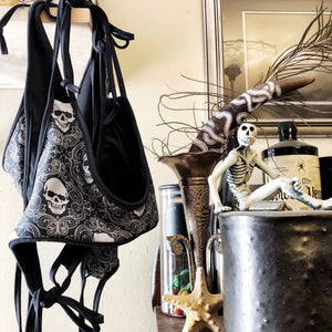 Reversible black and skull print bikini hanging next to skull and skeleton artwork