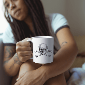 Woman holding white coffee mug with skull and crossbones