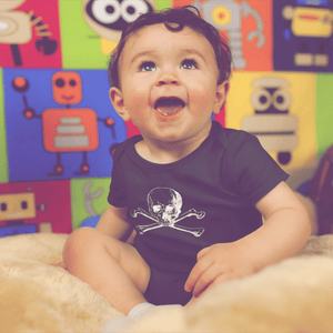 Baby smiling wearing skull and crossbones onesie in black