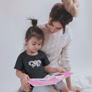 Child with skull and tentacle youth shirt sits on woman's lap reading a book