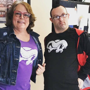 Woman and young man wearing purple and black skull and tentacle shirts with jackets