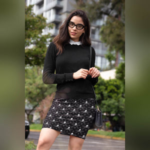 person with skull and crossbones pencil skirt, black sweater, and black rimmed glasses and long hair stand outside with purse.