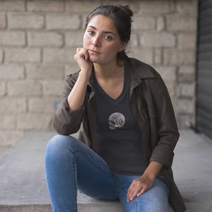 Woman sitting in jeans and spiral skull print v-neck t-shirt