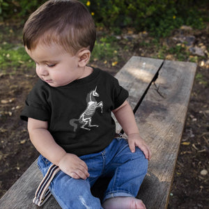 toddler with brown hair sits on a bench in jeans and a black unicorn skeleton baby onesie
