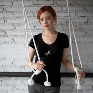 woman in unicorn skeleton deep v-neck t-shirt and grey leggings holds stretching cords at the gym
