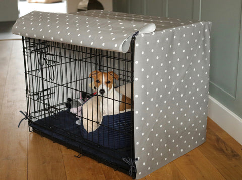 Jack Russell puppy in dog crate with grey oilcloth crate cover
