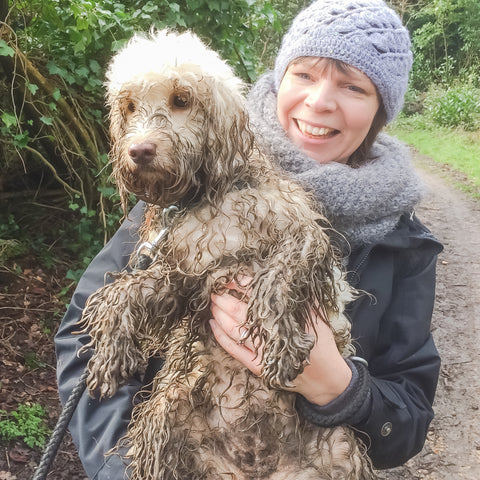 Very muddy dog being help by lady lauching. The Cosy Canine Company