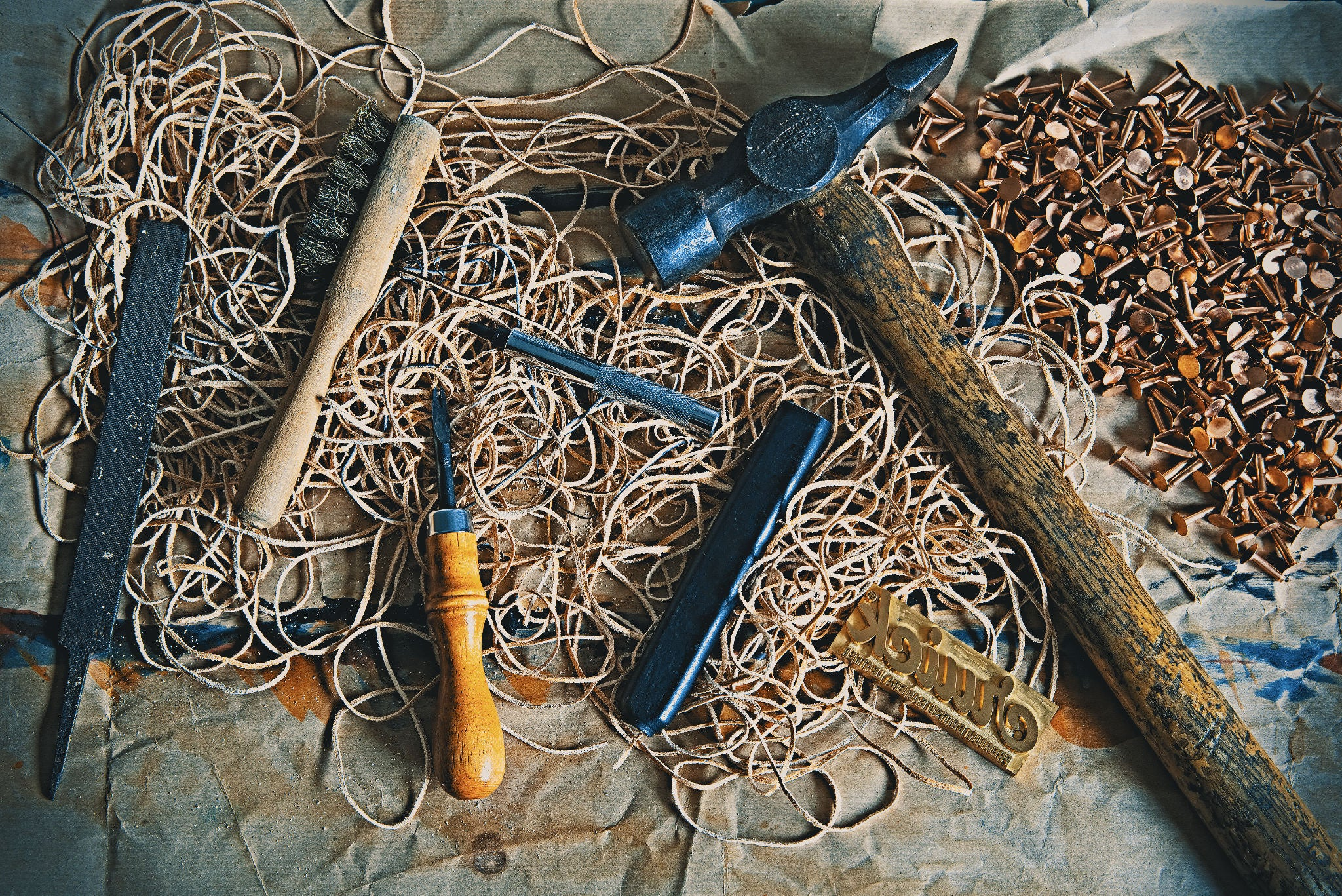 A collection of leather hand tools and copper rivets used for making Cruick camera straps.
