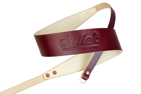 Cruick Luxus Pro camera strap in British Oxblood coiled to show napped lining and copper rivets.