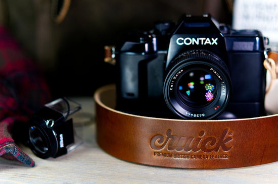 Cruick Luxus Pro camera strap in Oak & Umber Brown on a Contax film SLR camera next to Nikon loupe.