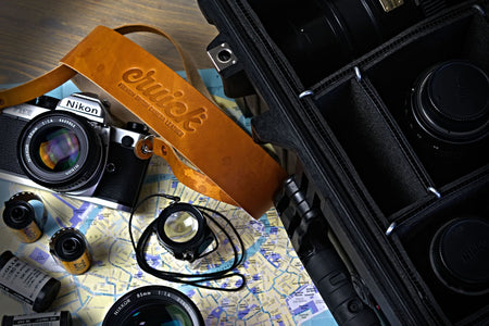 Cruick Luxus Pro camera strap in Sepia Tan on a Nikon FM2 film camera next to Nikkor f1.8 lens and Peli case.