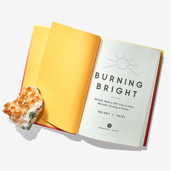 Burning Bright (Rituals, Reiki, and Self-Care to Heal Burnout, Anxiety, and Stress) by Kelsey J. Patel with a Citrine crystal.