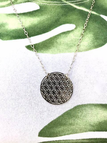 PEBBLE + ROSE flower of life pendant necklace shown on tropical material background