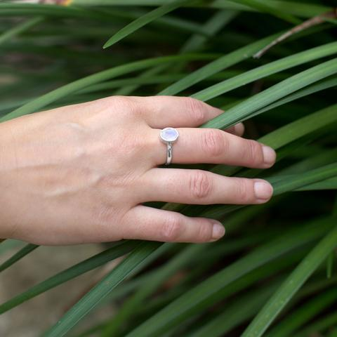 PEBBLE + ROSE Stackable Moonstone Ring on model's hand with tropical foliage