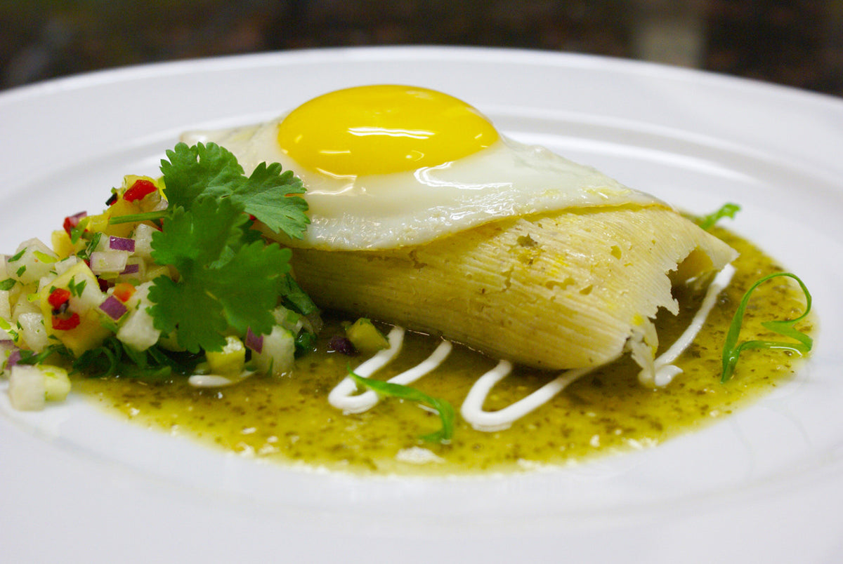 Sunny side up egg on tamale with tangy sauce