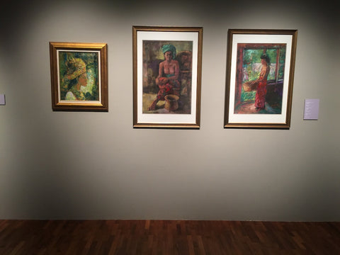Art exhibition in Singapore. ARTualize is the only art gallery in Singapore that lets you rent paintings for your home. Three paintings are hung on the wall in an art exhibtion.  One painting shows a Balinese woman  holding a basket, another painting shows a Balinese woman resting after her farming activities, the third shows a Balinese woman in traditional headgear.