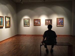 ARTualize is the only art gallery in Singapore that lets you rent paintings for your home.  Our mission is to help people realise the power of paintings.  A man is sitting on a bench looking at the paintings on the wall that are shone with spot light.