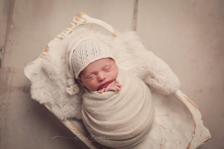 newborn baby in white trench bowl with white rabbit skin pelt prop