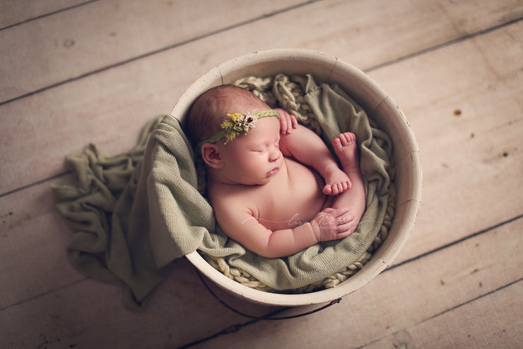 light green chunky blanket under baby in bowl with other props