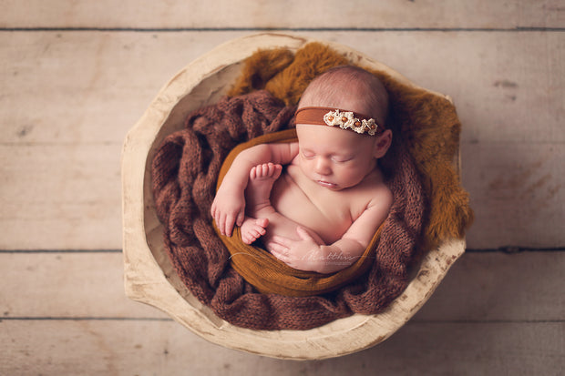 newborn baby girl in copper brown headband, swaddling wrap and fur photo prop