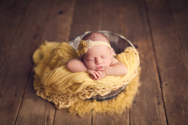 newborn baby girl headband in yellow, fur, swaddling wrap, chunky blanket and flokati fur photography props
