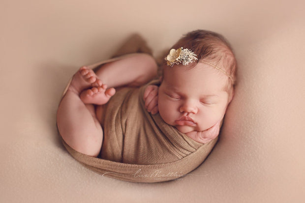 brown stretch swaddle wrap on newborn girl