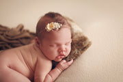 newborn baby girl with head on brown mini fur pillow and brown wrap