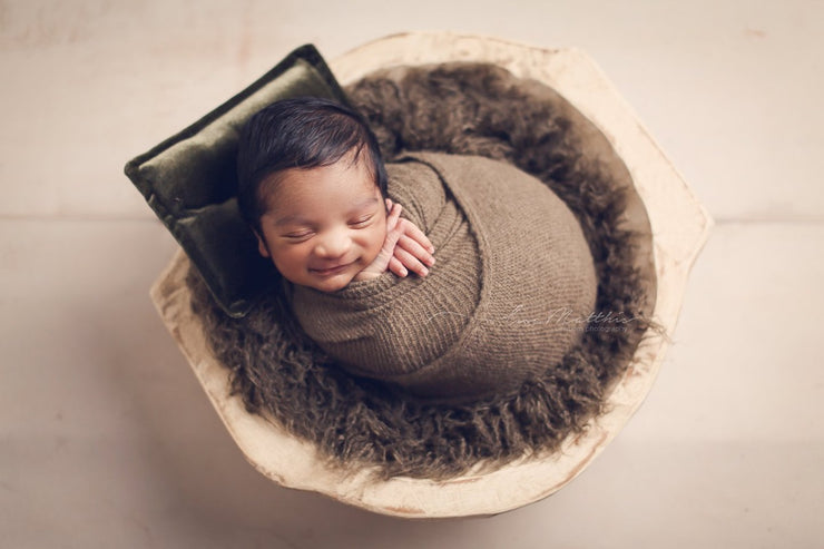 wavy newborn baby faux fur in brown with baby swaddled in brown wrap and dark green pillow in wood bowl