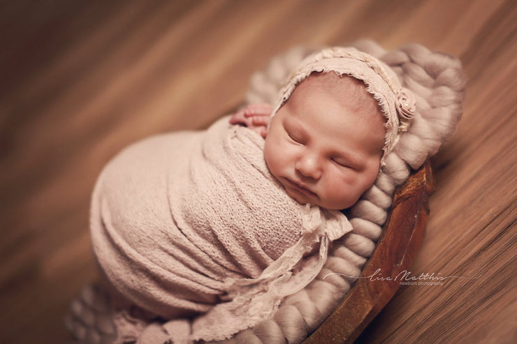 Baby boy swaddled in white baby wrap with relaxed swaddler sack photography prop