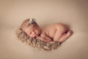 newborn girl with light tan or brown curly faux fur wool rug under neath