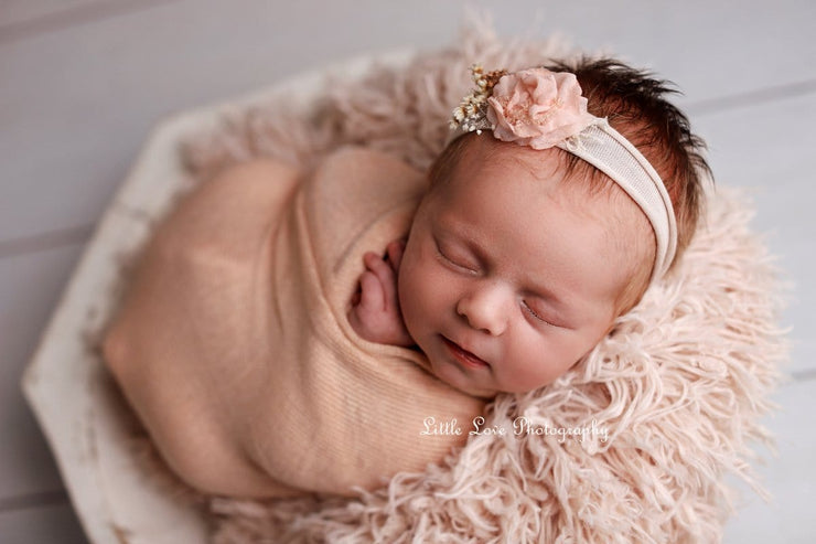 light peach newborn baby girl swaddled in swaddling wrap, bowl, fur and matching headband