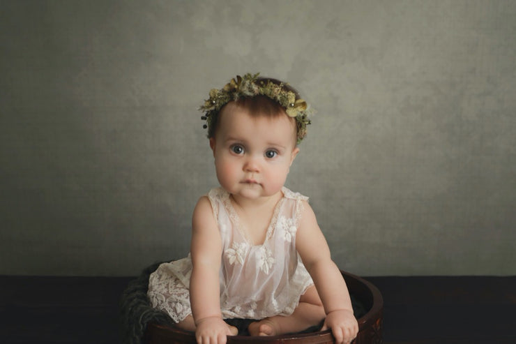sitter girl at 6 months old wearing green floral halo for baby pictures