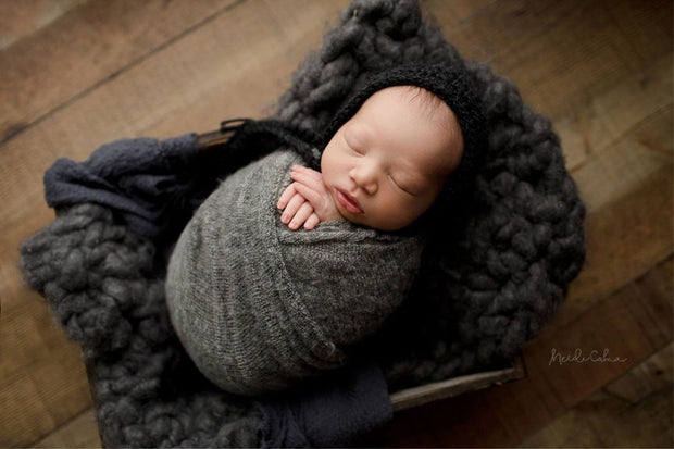 newborn baby boy swaddled in dark gray fuzzy sweater swaddle wrap. American made baby wrap by Custom Photo Props.