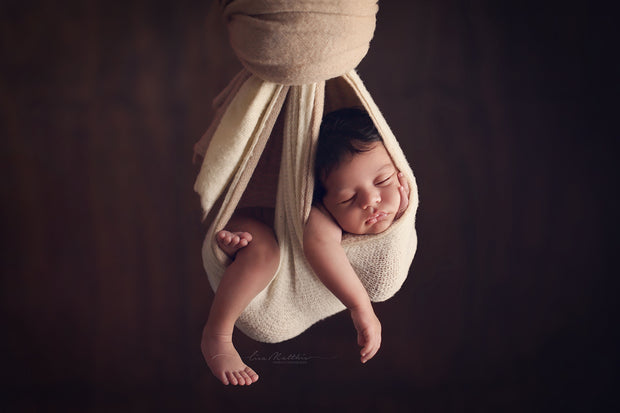 cream and beige newborn baby hanging in swaddling hammock photography prop